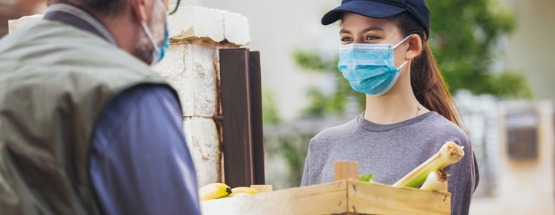 A young woman wearing a hat and a face mask is delivering groceries