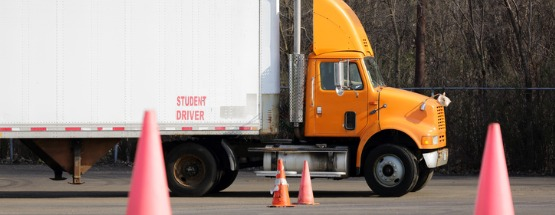 Student driver in a yellow semi-truck training in parking maneuvers
