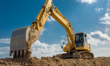 Large yellow excavator on a construction site on a sunny day