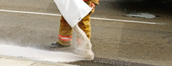firefighter pouring absorbent material on a fuel spill
