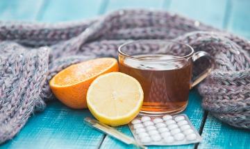 Cold and allergy pills, citrus fruit, and a mug of tea in front of a scarf