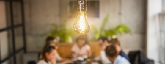Bright Light bulb hanging from a ceiling above a table of young innovators