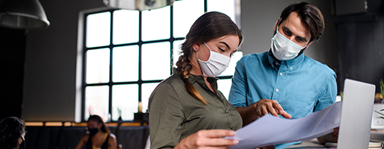 A man and woman wearing medical masks standing in front of a laptop while reviewing a large paper document