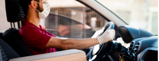 hispanic male courier in red shirt and facemask and gloves with orders in car delivery service