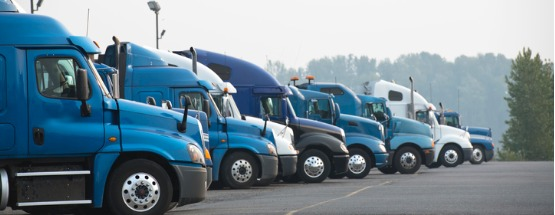 Profiles of blue and white big rig long haul semi trucks with high cab lined up in a parking lot