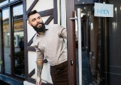 Happy bearded small business owner standing at doorway with an open sign