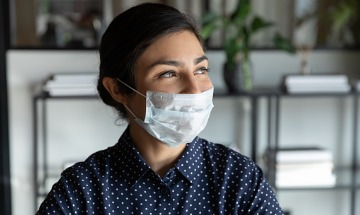 Happy young woman wearing a protective mask
