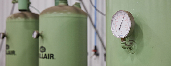Closeup of boiler pressure gauge with two pale green boilers in the background