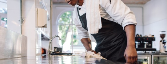 waiter wiping the counter top in a cafe kitchen with a cloth